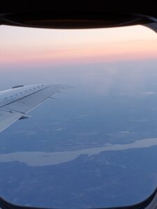 Early morning sky with plane wing outside window
